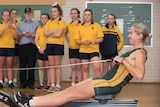 a woman in rowing uniform goes through her paces on a rowing machine while students watch on