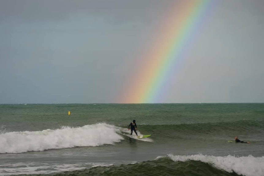 Surfer rides wave in front of rainbow