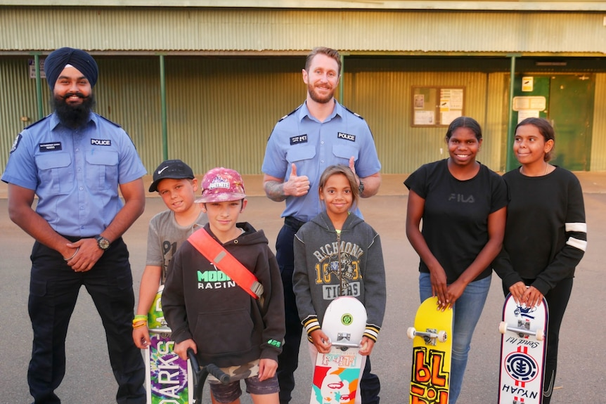 Two police officers smiling with five children at a skate park.