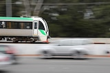 A Transperth train travels from left to right with blurry cars heading in the opposite direction in the foreground.