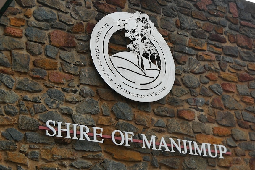 A brick wall with a shire office logo in the middle and 'Shire of Manjimup' written underneath