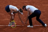 A female tennis player and the umpire bend over to inspect the clay for a mark on match point at the French Open.