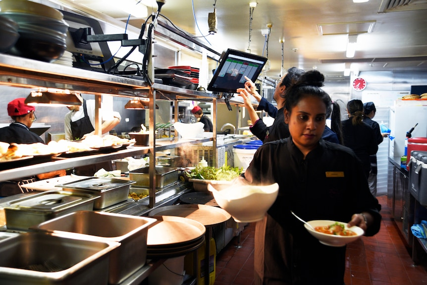 A waitress takes out plates of food from the kitchen at Darwin restaurant, Hanuman.