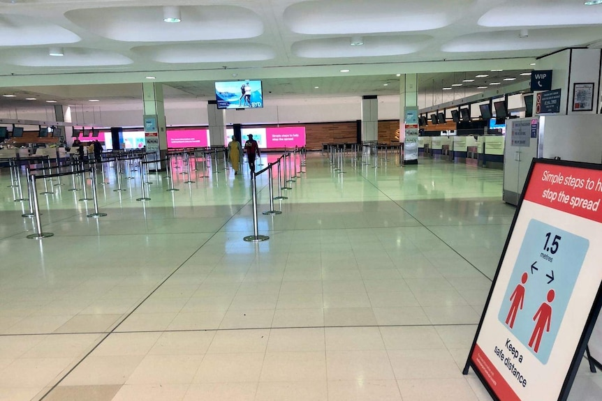 Airport walkways are empty with a sign in the foreground about social distancing