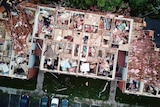 This aerial photo shows a roof blown off a building and rubble in an apartment complex.
