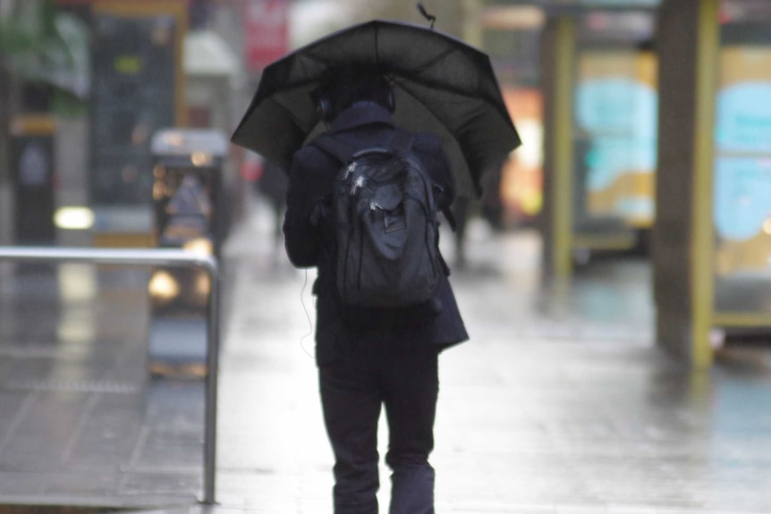A man in black carrying a backpack walks down a city street in the rain holding an umbrella.
