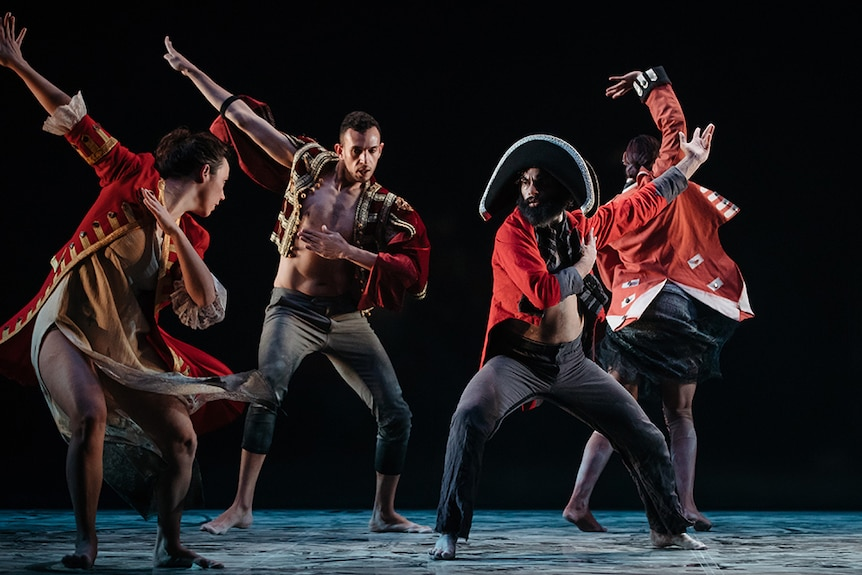 Four male dancers wear red and black colonial style costumes perform on stage with arms raised.