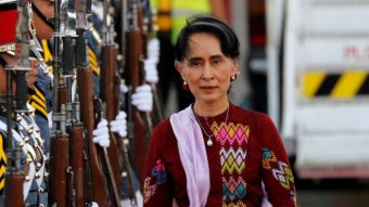 Aung San Suu Kyi walking alongside a row of soldiers holding guns