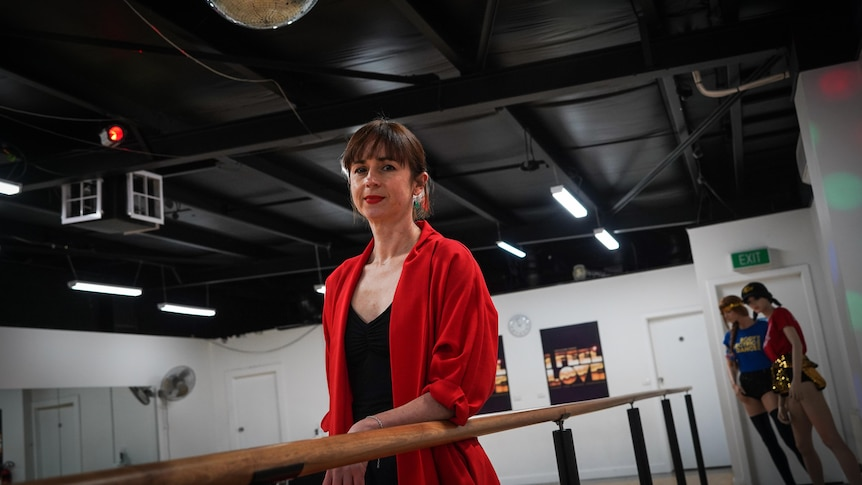 Jade Duffy, in a red blazer, stands in a dance studio looking at the camera.