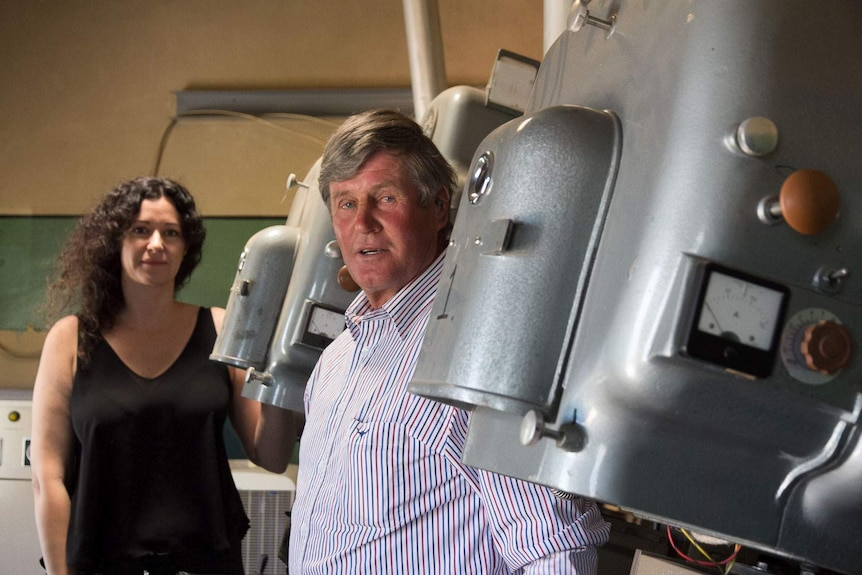 A man and woman standing next to huge old movie projectors