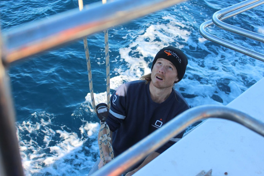 A man stands on a boat looking upwards