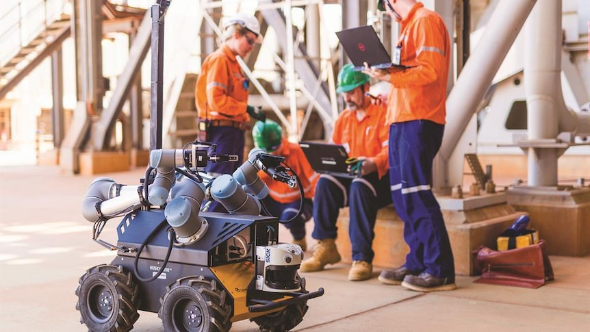 Workers on a mine site control a small, wheeled robot using a laptop
