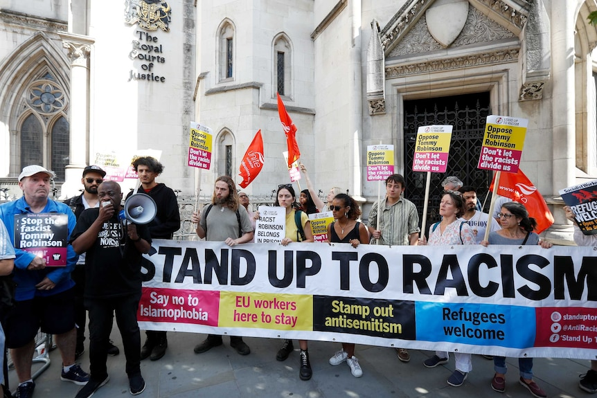 """Protesters hold up placards saying """"Oppose Tommy Robinson"""" and hold a banner saying """"Stand up to racism""""."""