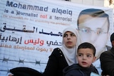 The wife of Palestinian imprisoned journalist Mohammed al-Qiq, Fayha Shalash, with her son Islam