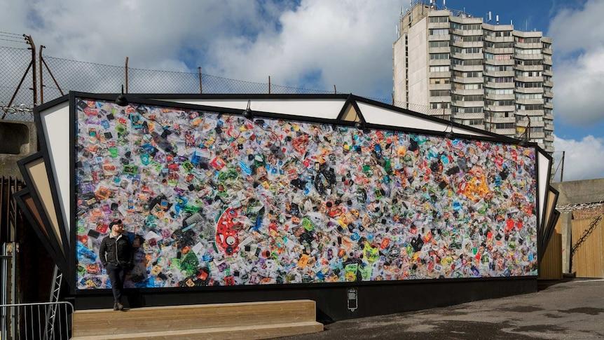 Daniel Webb stands beside his installation 'Everyday Plastic'