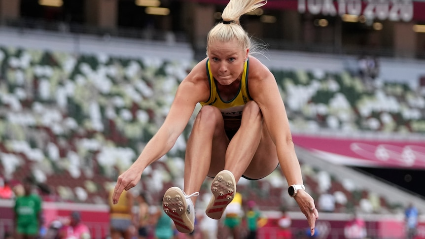 An Australian female athlete flies through the air with her arms and legs stretched out in the long jump.
