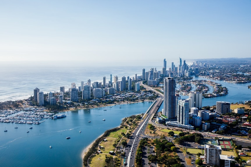 An aerial image showing a waterway, the Gold Coast skyline and the ocean behind on a clear, sunny day.