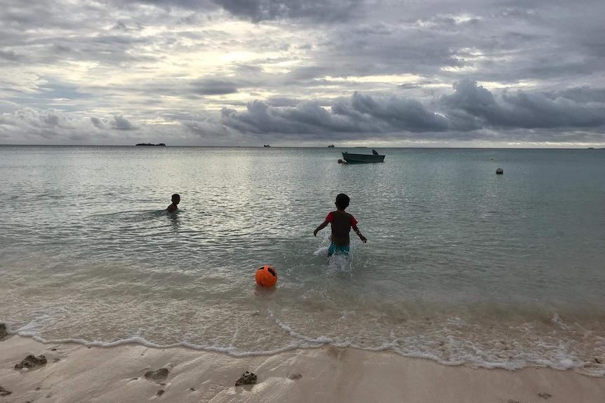 Children play in the waters of Tuvalu's biggest atoll Funafuti.