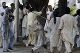 Pakistani religious students throw stones at paramilitary troopers during clashes outside the Red Mosque