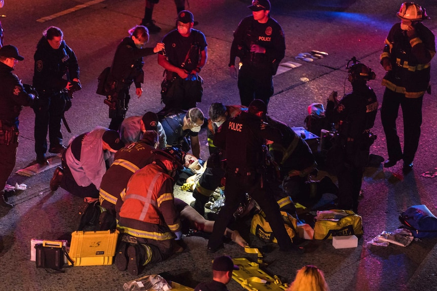 A woman is treated for injuries on the ground at night as a group of emergency workers surround her.