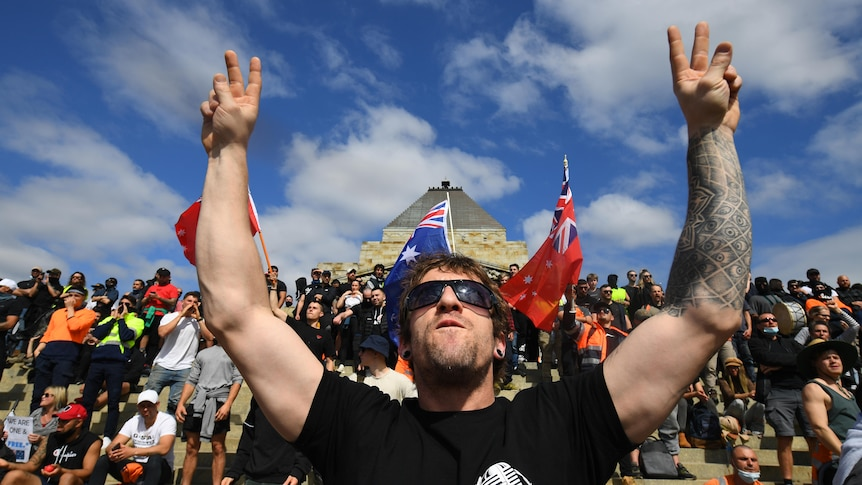 A man with sleeve tattoo on one of his arm makes a victory sign with lots of people sitting behind him and flag of Australia