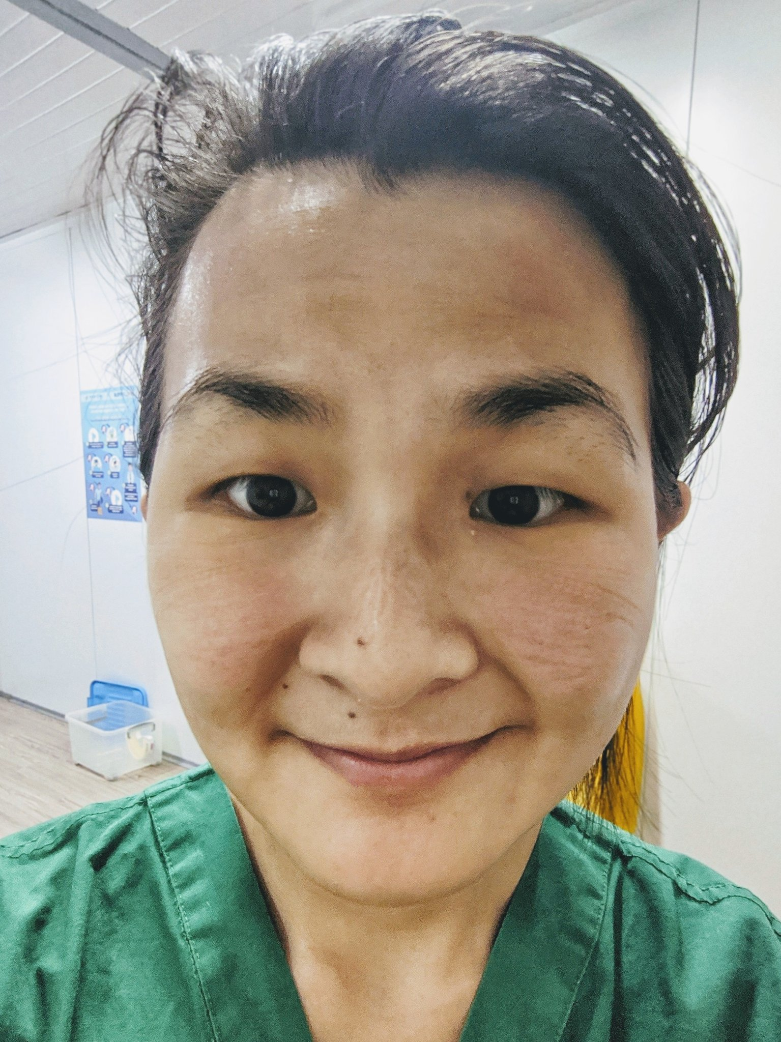 A female doctor takes a selfie with markings on her face from goggles