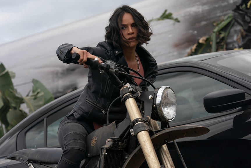 Michelle Rodriguez on a motorcycle, tensed forward, in Fast and Furious 9