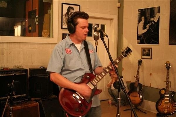 Charlie sings, wearing headphones and playing a guitar, black and white posters behind him.