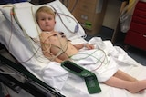 Four-year-old boy lying in hospital bed looking at camera, leg bandaged.