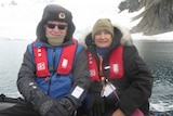 Bev and John Kable sit on a boat on water in front of ice and snow.