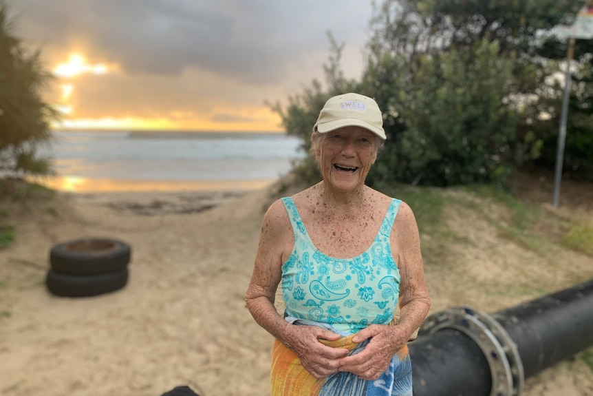 A woman wearing a tan cap and a blue swimsuit smiles while standing at the entryway of the beach lit by a golden sunrise