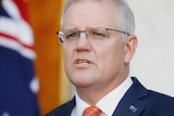 Morrison looks up in concentration as he's speaking at a press conference