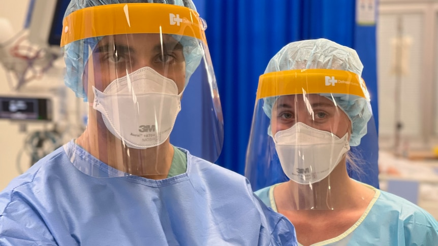 A male and female nurse standing, wearing full PPE.