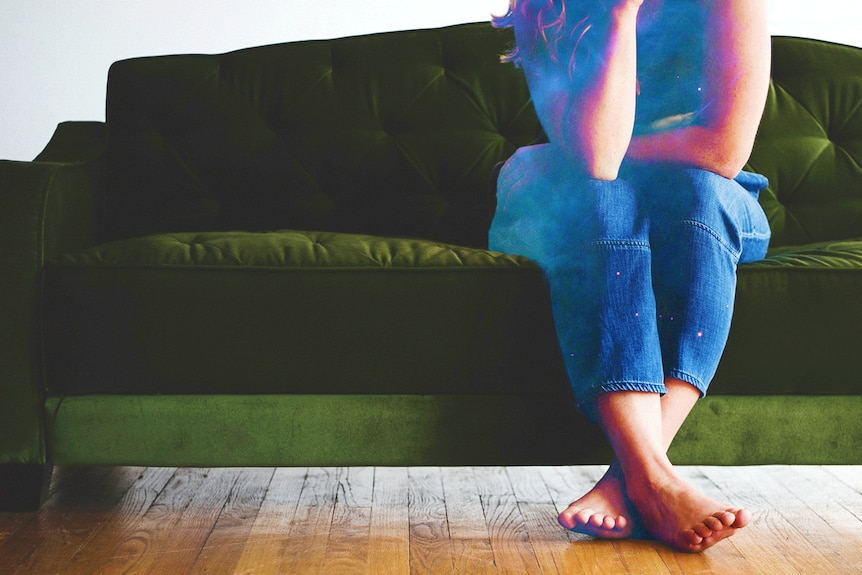 Woman sitting on a green couch looking lonely.