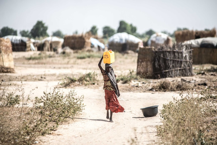 A girl walks to collect water from a Save the Children water point in the informal displacement camp at Musari
