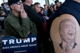Tattoo of Donald Trump's face on a supporter's upper arm with another supporter holding a sign reading TRUMP.