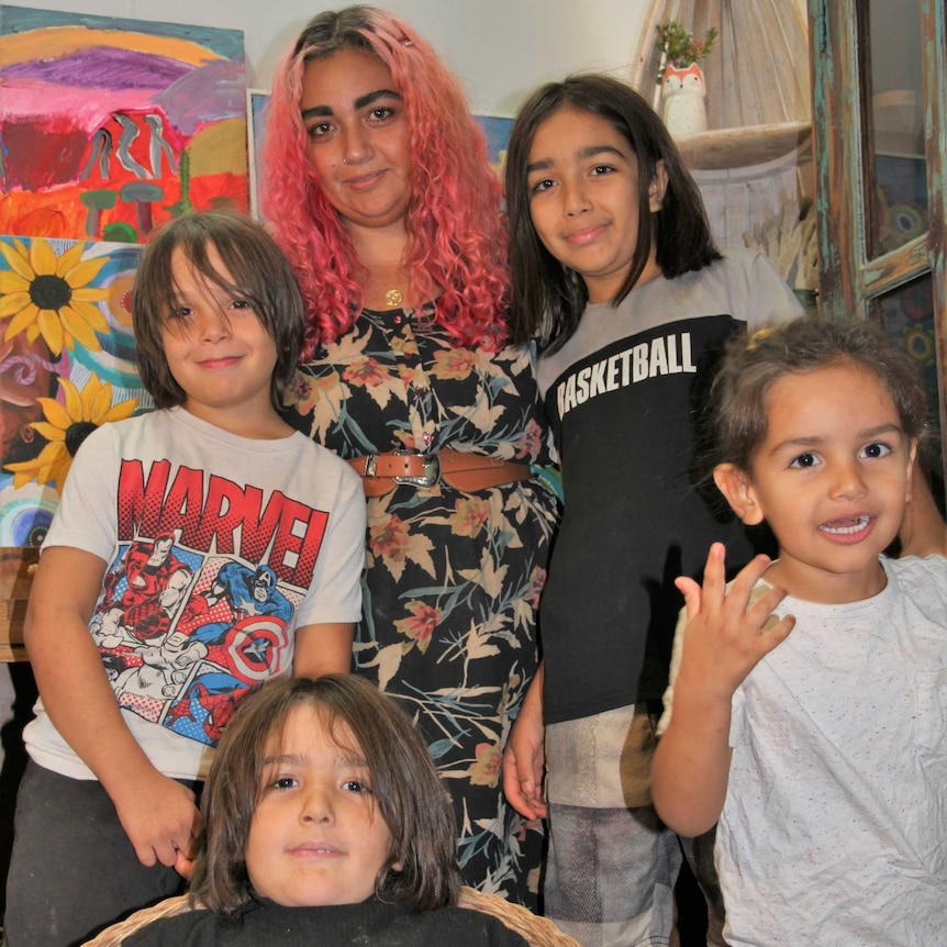 A woman with pink wavy hair stands behind four young boys
