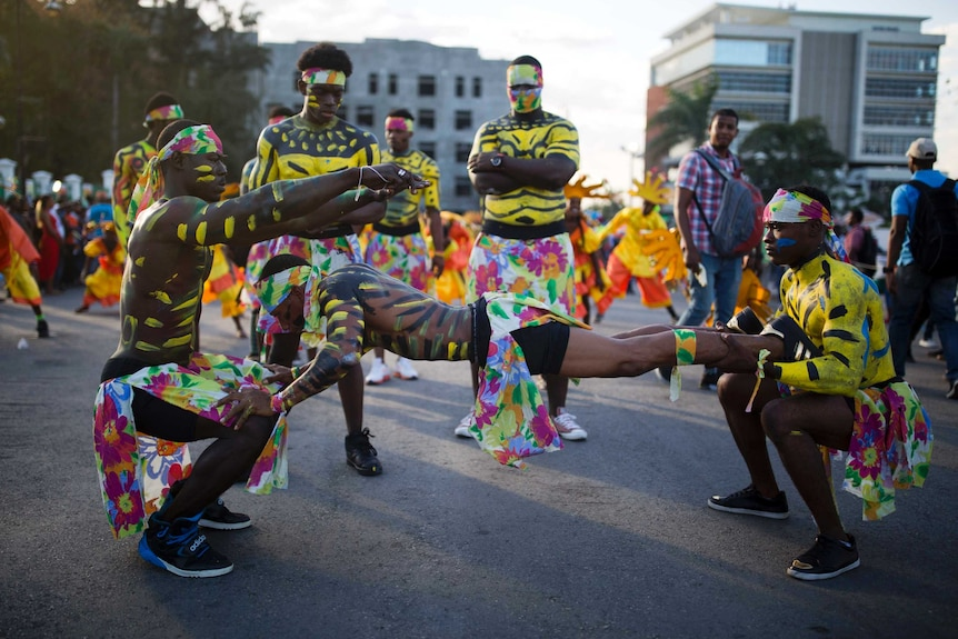 Men in body paint and multicoloured costumes perform in the street during Carnival in Haiti.