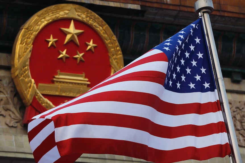 The US flag is waving in front of the red and gold round symbol of China.