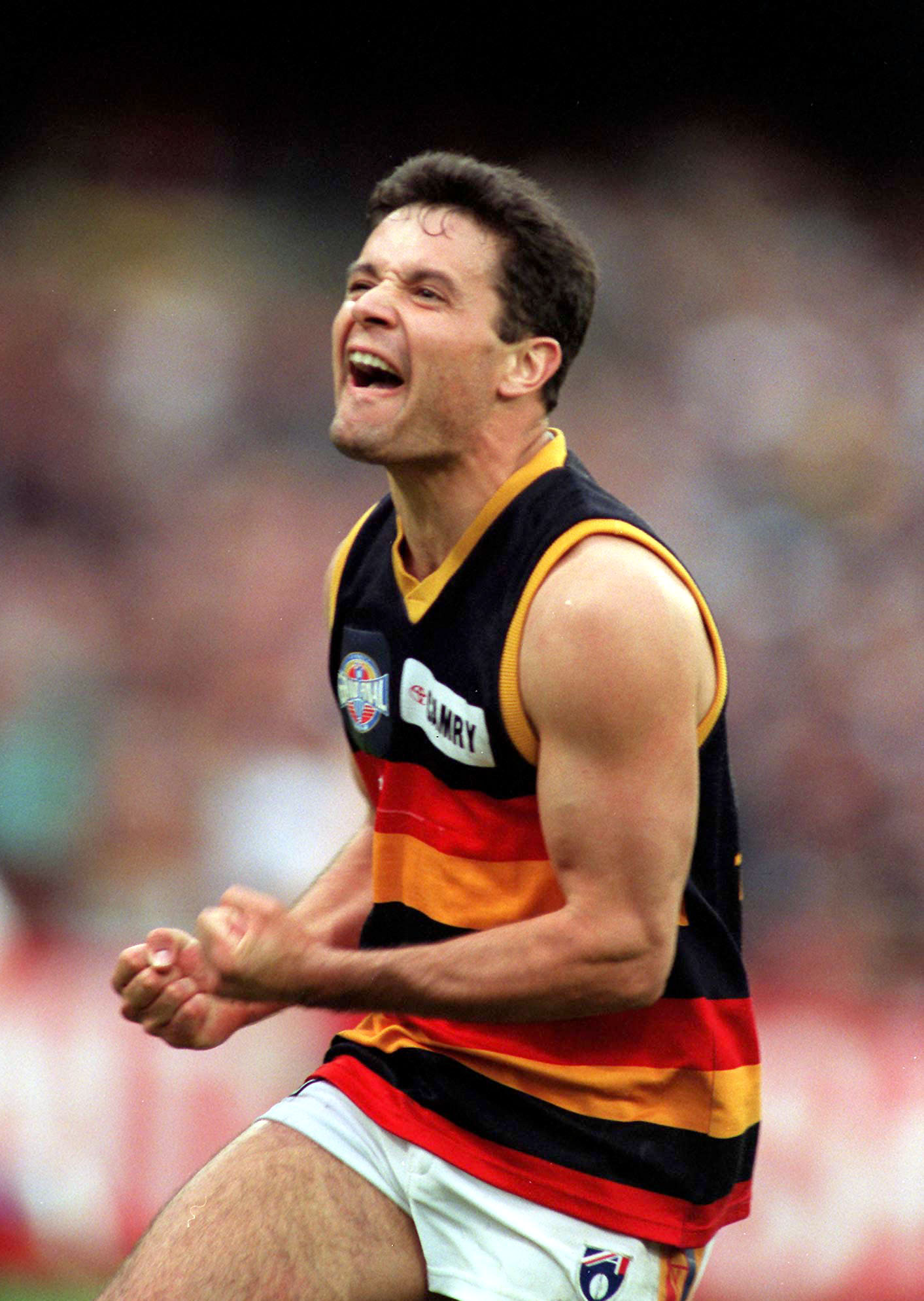 A footballer screams in a joy while wearing a yellow, red and blue jumper.