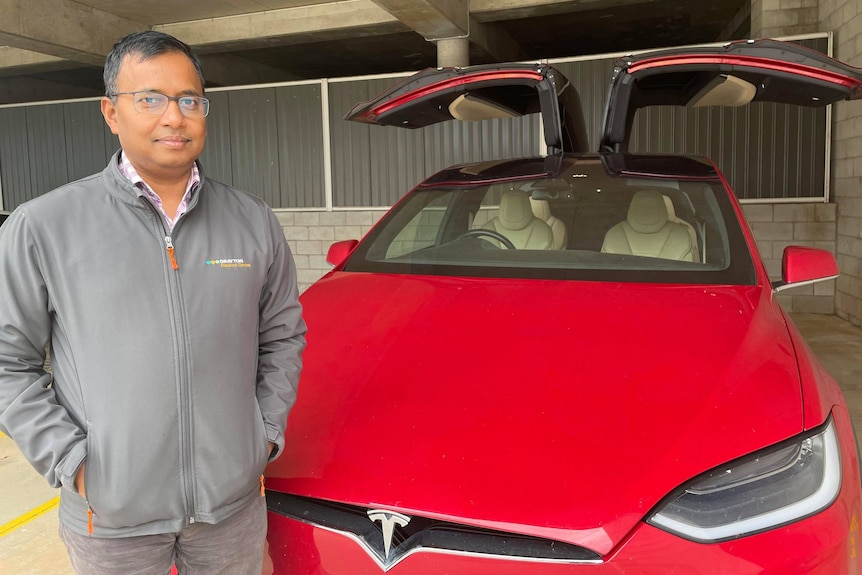 A man standing in front of a red electric car.