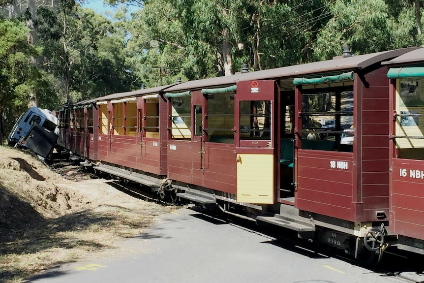 The Puffing Billy train sits stopped on the tracks next to a minibus.