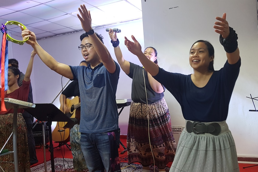 Four people stand on a stage holding their hands up in the air.