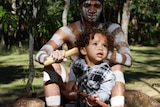 A father, in warrior pant, sits with his child.