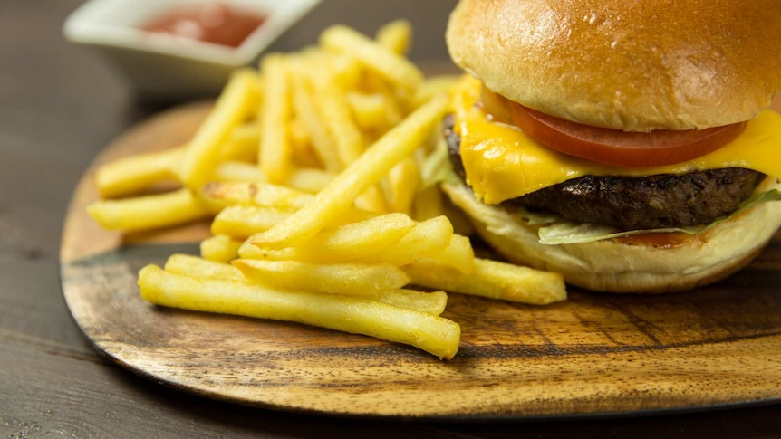 A burger and chips served on a wooden board.