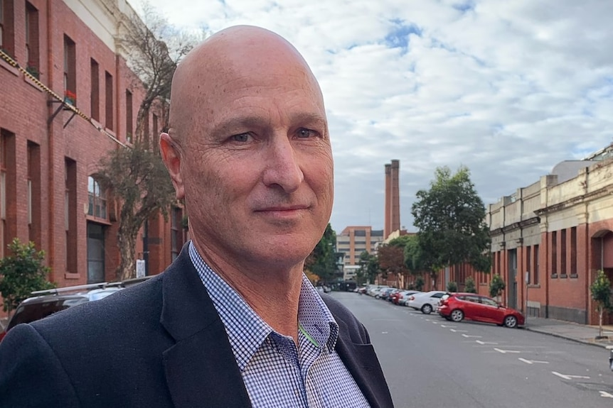 A bald man wearing a suit jacket and shirt stands in a quiet street.
