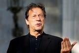 Imran Khan wearing a black shirt speaks as he raises his left hand up palm upwards