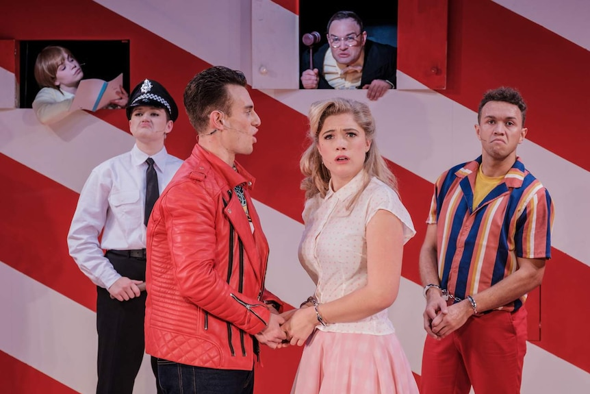 Production still showing six actors in 50s-style clothing on a colourful pink and red set.