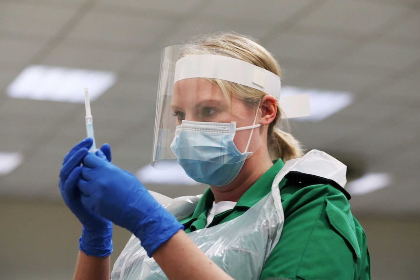 A woman in a face mask and clear shield examines