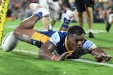 A Parramatta Eels NRL player dives to score a try against Brisbane.
